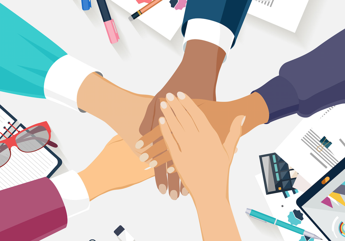 Five People's Hands Coming Together Above Desk with Office Items on It